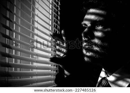 Man looks through blinds from a dark room - stock photo