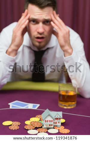 Man losing his house at poker game in casino - stock photo