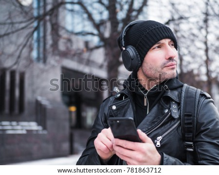 Man lost in unknown city. he is dressed in a leather jacket, hat and headphones