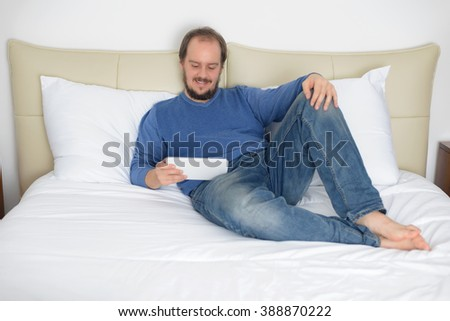 Man lying bed holding tablet computer smiling