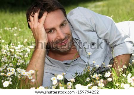 Man lying in a field - stock photo