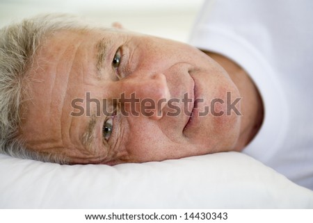 Man lying in bed - stock photo