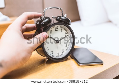 Man lying in bed turning off an alarm clock in the morning  - stock photo