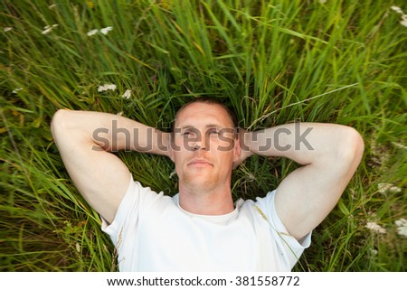 Man lying in   grass with   arms behind   head.