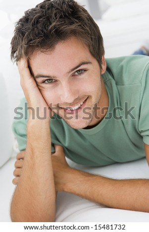 Man lying in living room smiling - stock photo