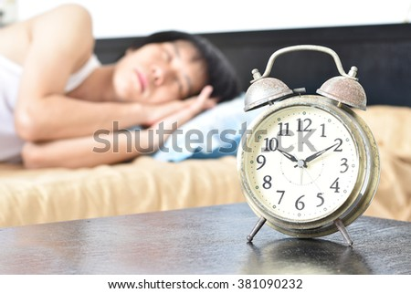 Man lying in white bed with silver alarm clock