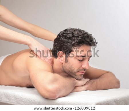Man lying on a massage table is massaged by two female hands - stock photo