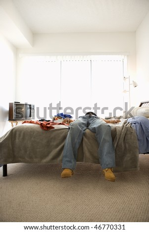 Man lying on bed. Only his lower body is viewable. Vertical shot. - stock photo