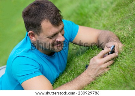 Man lying on grass with mobile smart phone and writing sms