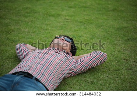 Man lying on green grass wearing check shirt, blue jeans at a park and looking on the sky on summer day - stock photo