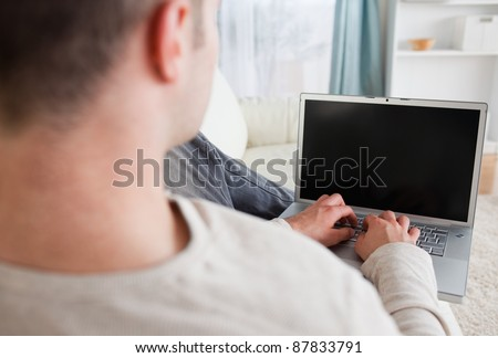 Man lying on his couch while using a laptop in his living room