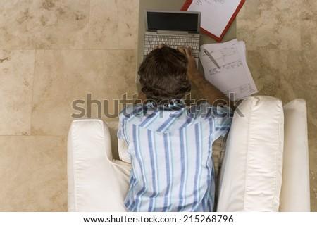 Man lying on sofa at home, using laptop resting on coffee table, overhead view - stock photo