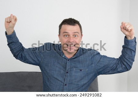 Man lying on sofa with arms in the air