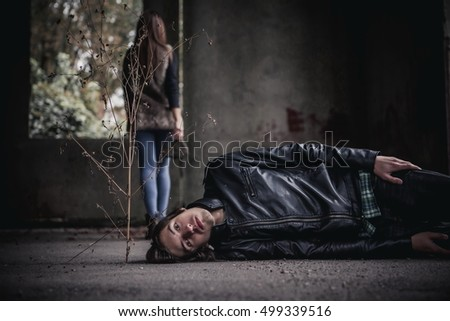 man lying on the ground. girl goes on a background