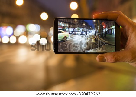 Man makes a picture in the street with his mobile phone. Night light bokeh background - stock photo
