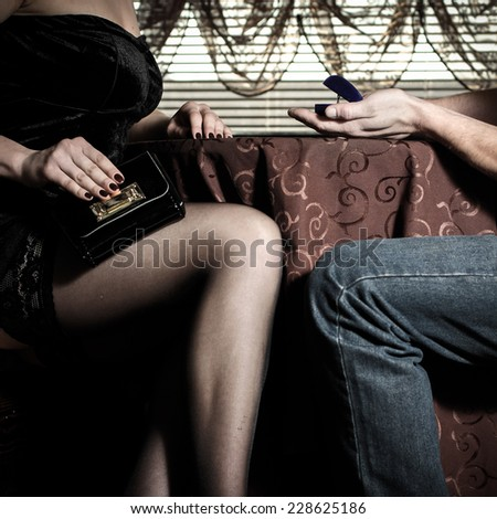 man makes an offer to marry the woman in the cafe. Closeup of male and female legs and hands during a date - stock photo