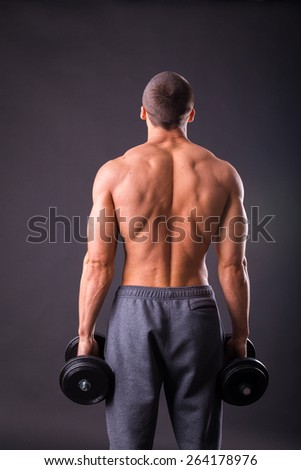 Man makes exercises dumbbells. Sport, power, dumbbells, tension, exercise. Article about fitness and sports.Gym and fitness concept - bodybuilder and dumbbell over black.