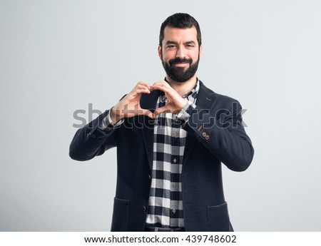 Man making a heart with his hands over grey background - stock photo