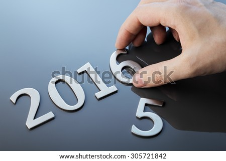 Man making number 2016 with metallic numbers. - stock photo