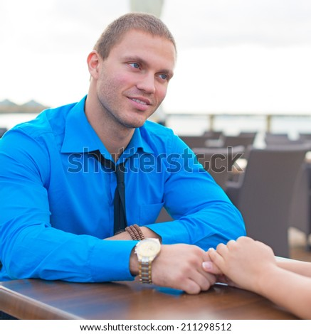 Man making proposal to woman in outdoor cafe. - stock photo
