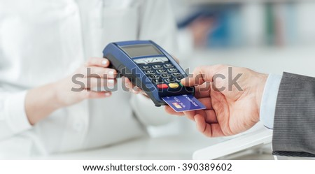Man making purchases at the drugstore, he is paying with a credit card and using a terminal - stock photo