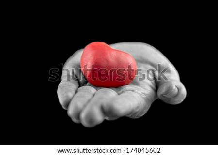 Man making the gift of Love to his sweetheart on Valentines Day offering a red heart in his outstretched hand, greyscale image with selective red colour - stock photo