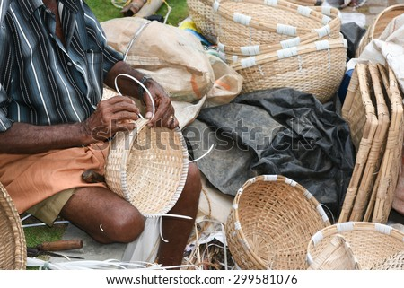 man making traditional bamboo cane furniture , handicrafts on display during the Handicraft Fair in Kerala, hand made kitchen utensils - stock photo