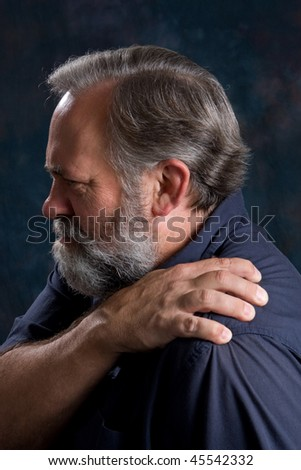 Man massages his painful shoulder. - stock photo