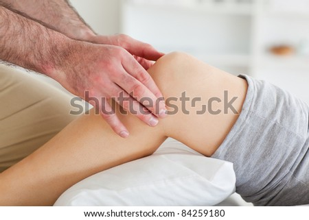 Man massaging a lying woman's knee in a room - stock photo