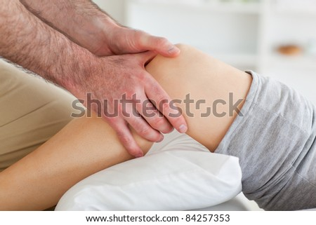 Man massaging a woman's knee in a room - stock photo
