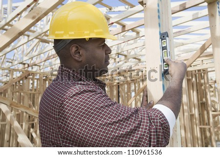 Man measuring form work at construction site