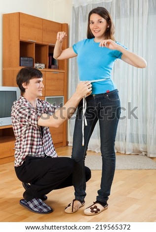 Man measuring girlriend waist with measuring tape - stock photo