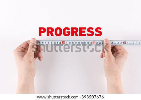 Man measuring PROGRESS - stock photo