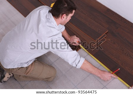 Man measuring wooden flooring - stock photo