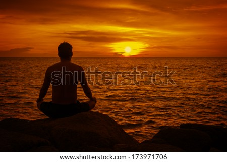 Man meditating at sunset. Tropical beach in Thailand
