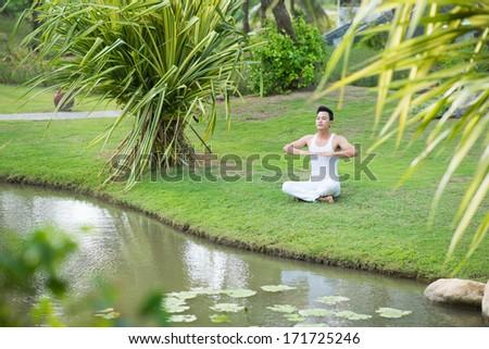 Man meditating at the river - stock photo