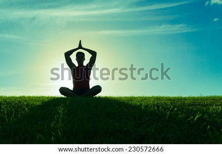 Man meditating in a yoga pose outdoors - stock photo