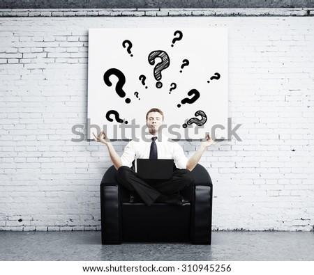 man meditating in brick room - stock photo