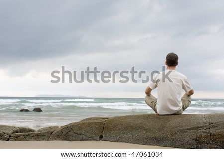 Man meditating on a rock at the sea