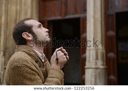 man monk praying to the front door of the church holding cross crucifix - stock photo