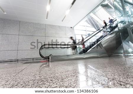 Man move in glass corridor in airport - stock photo