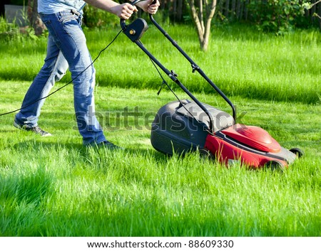 Man moves with lawnmower &  mows green grass - stock photo