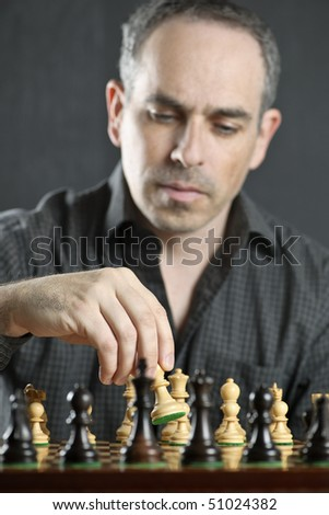 Man moving a chess pawn on wooden chessboard as first move - stock photo