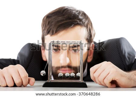 Man moving newton balls in office. - stock photo
