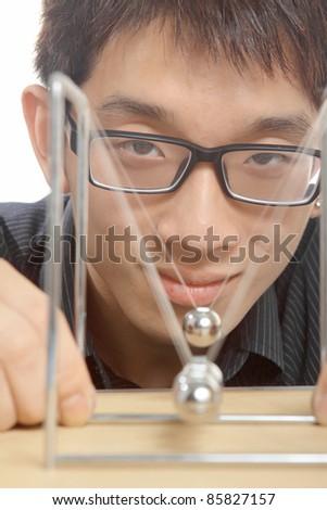 man moving Newton balls in office - stock photo