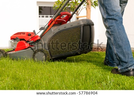 Man mowing lawn in his garden or front yard in summer
