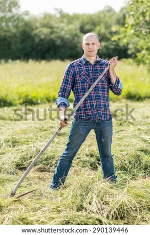 Man mowing old fashioned way with a scythe