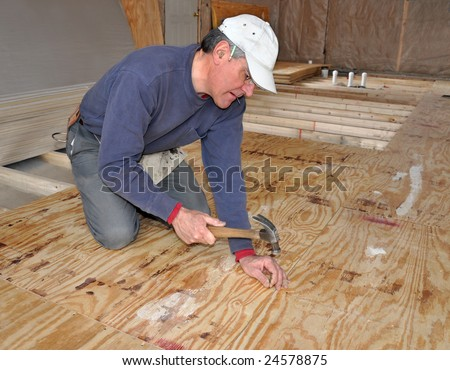 Man nailing down plywood sub-floor - stock photo