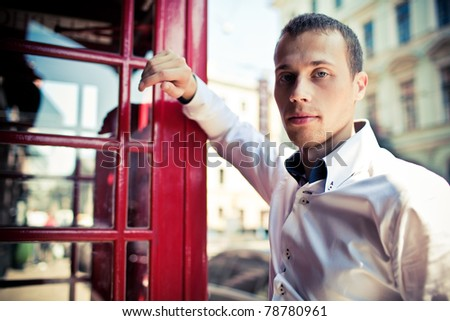 man next to the typical red London phone boot - stock photo