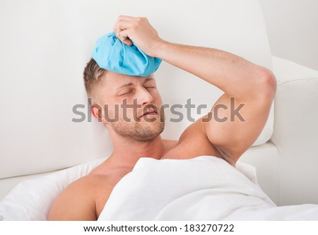 Man nursing a hangover after a heavy night of partying holding an ice pack to his forehead with his eyes closed on pain against the throbbing - stock photo
